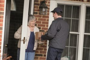 elderly female receiving medical supplies at home from delivery man